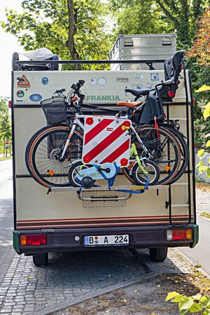 Berlin, Germany - August 26, 2018: A camping van with a cycle carrier attached to the rear with two bicycles with infant seat and a child's bike.