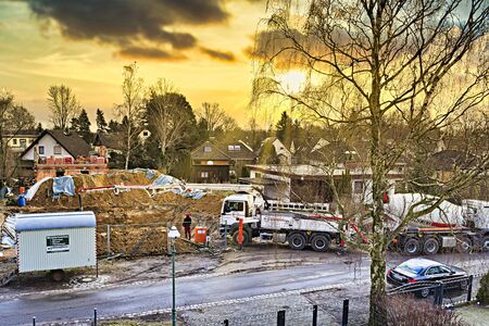 Berlin, Germany - March 9, 2018: Mobile concrete pump on a construction site at making the ground floor of a house in front of a wonderful sunset.