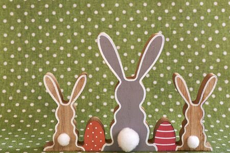 Three wooden Easter bunnies from behind with painted decoration.