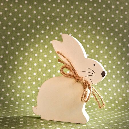 Wooden Easter bunny in front of a green background with white dots. Stockfoto
