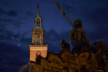 Lighted spire of the historic St. Marienchurch behind the Neptune's Fountain in the center of Berlin at night. Stockfoto