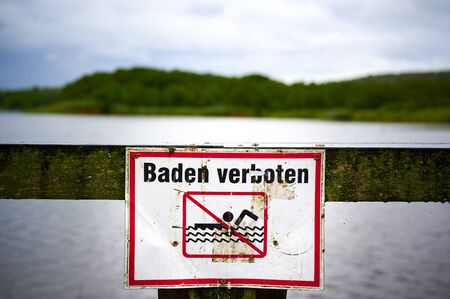 Sign with a pictogram that prohibits swimming. The text means bathing prohibited in German. Stock fotó