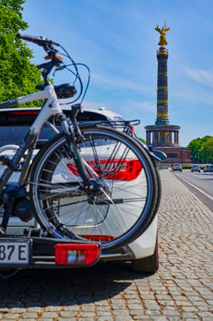 Berlin, Germany - May 8, 2020: Unfocussed parked car with a bike carrier attached to the stern and bicycles mounted on it. In the background you see the Berlin Siegessaeule, a historic landmark.