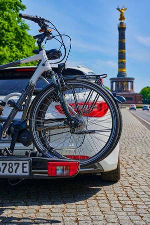 Berlin, Germany - May 8, 2020: Parked car with a bike carrier attached to the stern and bicycles mounted on it. In the background you see the unfocussed Berlin Siegessaeule, a historic landmark. Editorial