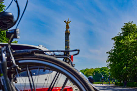 Berlin, Germany - May 8, 2020: Unfocussed parked car with a bike carrier attached to the stern and bicycles mounted on it. In the background you see the Berlin Siegessaeule, a historic landmark. Standard-Bild - 146908541