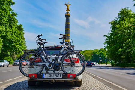 Berlin, Germany - May 8, 2020: Parked car with a bike carrier attached to the stern and bicycles mounted on it. In the background you see the unfocussed Berlin Siegessaeule, a historic landmark. Standard-Bild - 146908542
