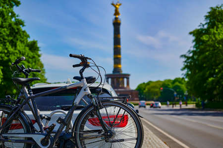 Berlin, Germany - May 8, 2020: Parked car with a bike carrier attached to the stern and bicycles mounted on it. In the background you see the unfocussed Berlin Siegessaeule, a historic landmark. Standard-Bild - 146908543