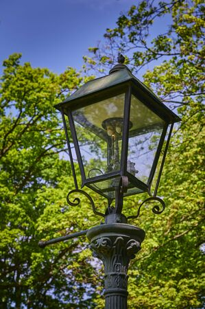 Historic and still functional street lamp that is powered by gas and stands in a Berlin park.