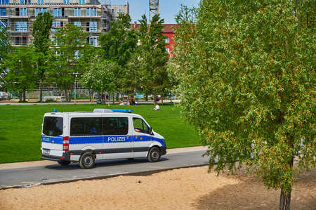 Berlin, Germany - May 10, 2020: Berlin police who check in a public park whether the distance rules due to the covid-19 pandemic are being observed.