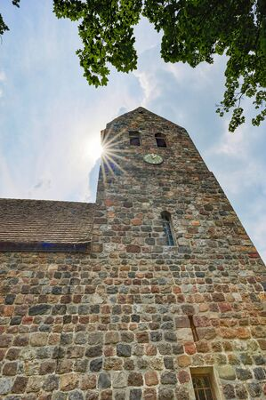Details of a historic medieval church in Berlin, Germany. You can see parts of the building with the church tower. Sunbeams can be seen near the tower.