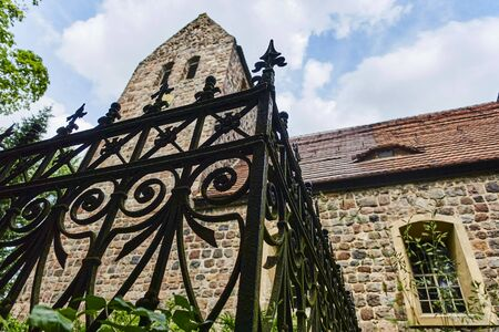 Details of a historic medieval church in Berlin, Germany. You can see a cast iron fence in front of the blurred church.