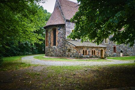 Details of a historic medieval church in Berlin, Germany. You can see parts of the building made of field stones, framed by trees.