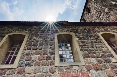 Details of a historic medieval church in Berlin, Germany. You can see the nave and the tower. Sunbeams can be seen above the roof.