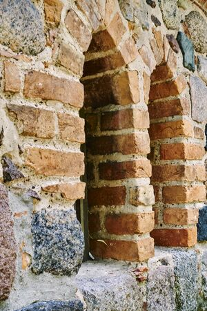 Details of a historic medieval church in Berlin, Germany. You can see a series of windows in a field stone wall.