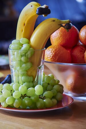 Bananas as dolphins with a dark grape in the mouth and green grapes and tangerines as a decoration.