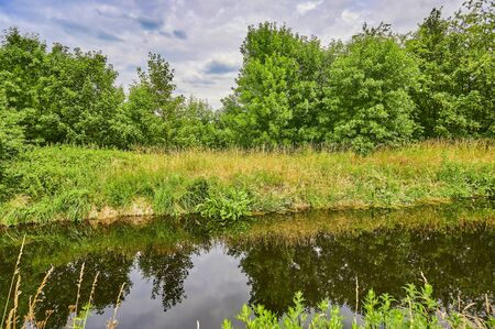 Cloudy sky over a little creek in the surrounding countryside of Berlin, Germany.