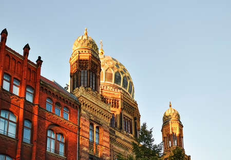 View to the dome and the small towers of New Synagogue in the downtown of Berlin in the evening sun.