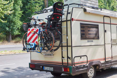 Berlin, Germany - August 26, 2018: A camper with a cycle carrier attached to the rear with two bicycles with infant seat and a child's bike. 新聞圖片
