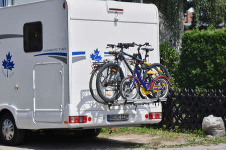 Berlin, Germany - July 30, 2018: A camper with a cycle carrier attached to the rear with two bicycles and a child's bike. 新聞圖片