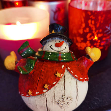A snowman as a Christmas decoration with unfocussed candles in the background.