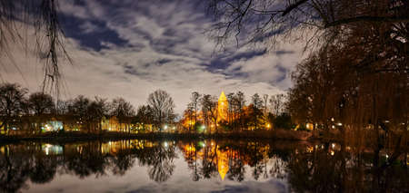 A historic village church that is illuminated by lamps in Berlin-Lichtenrade at night and that is reflected in a pond.