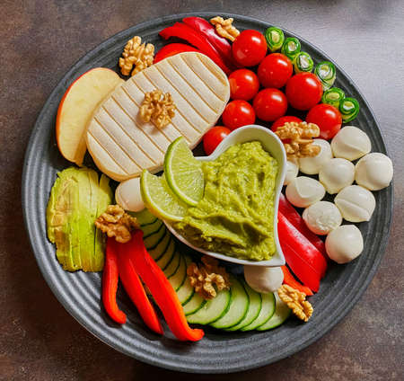 Photography from the top of to a plate with assorted colorful bread toppings and vegetables, which are arranged decoratively. Stock fotó