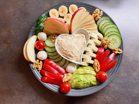 Photography from assorted colorful bread toppings and vegetables, which are arranged decoratively.