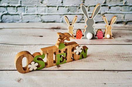Wooden sign with an Easter bunny with flowers as decoration. The text is German for Easter.
