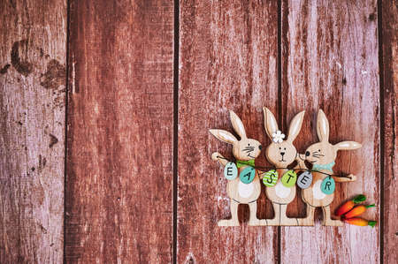 Wooden Easter bunnies with decoration and the text Easter written on eggs.
