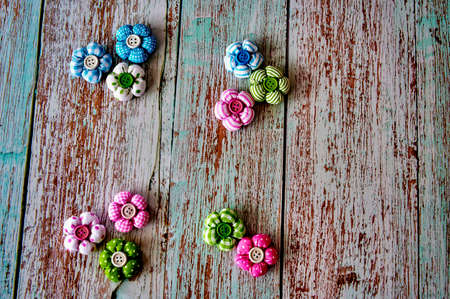 Easter decoration made of colorful fabric flowers with a button in the middle, lying on a wooden surface.