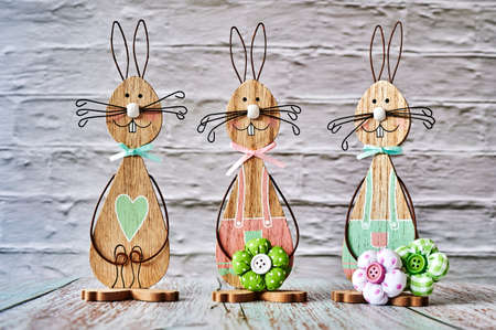 Three wooden Easter bunnies with decoration.