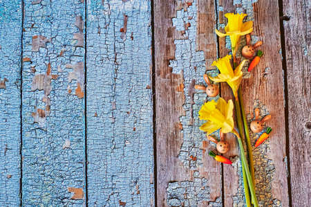 Three yellow jonquils with traditional Easter decoration.