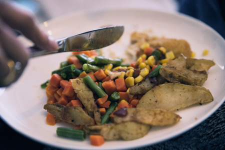 Wedges, carrots, corn and peas on a plate.