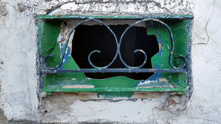 Old window in a Spanish house with green shutters and metal bars. Stone surround.