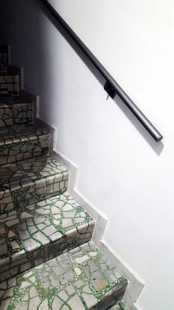 Green marble tile staircase with stainless steel handrail.