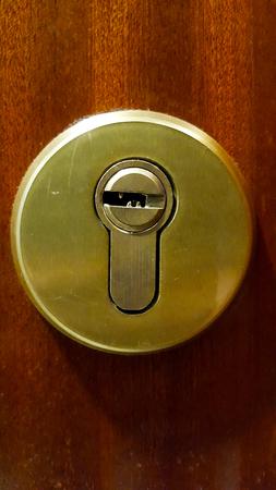 Brass lock on a brown wooden office door Imagens