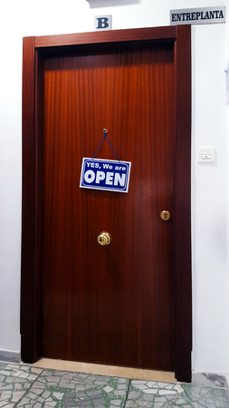 Brown flat door with a sign saying Yes We Are Open. Spanish building.