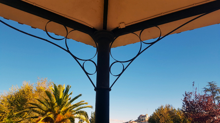 Decorative metal ceiling of a bandstand in a park with deep blue sky Imagens