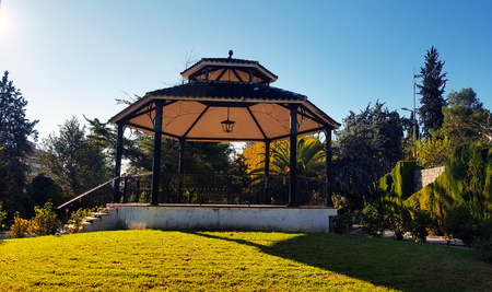 large bandstand in a well tended park with grass and trees in evening sunshine