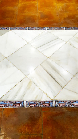 White stone marble floor with decorative blue border and brown tiles.