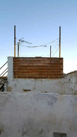 Terracotta brick construction on top of a building with white walls.
