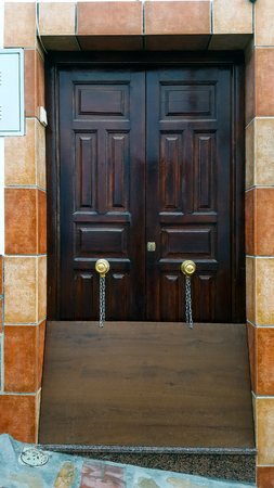Flat wooden board chained to a front door to deflect rainwater. Spanish house with wooden doors and tile surround