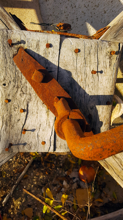 Old wooden wheel gear with rusty metal handle and brackets. Olive oil processing equipment. Garden wall in evening sunshine.