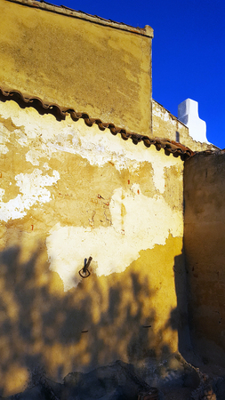 Spanish garden wall with deep blue sky and evening sun
