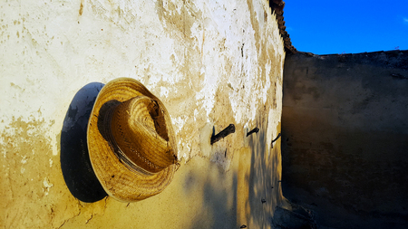 Spanish garden wall with deep blue sky and evening sun and old straw hat
