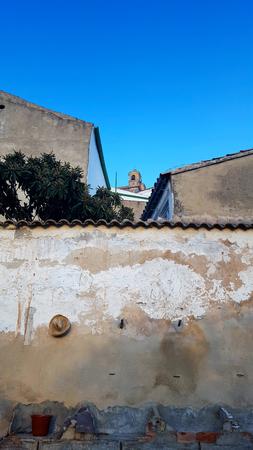 Spanish garden wall with Nispero, Medlar tree and church tower