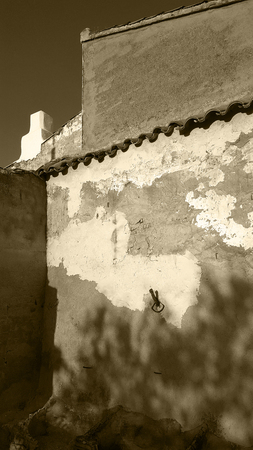 Spanish garden wall with deep blue sky and evening sun. Monochrome, sepia tone, black and white.