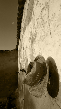 Spanish garden wall with deep blue sky and evening sun and old straw hat and moon. Monochrome, sepia tone, black and white. Imagens