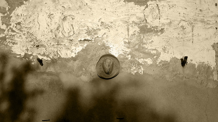 Spanish garden wall with deep blue sky and evening sun and old straw hat. Monochrome, sepia tone, black and white.