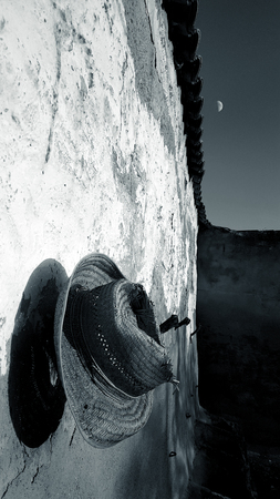 Spanish garden wall with deep blue sky and evening sun and old straw hat and moon